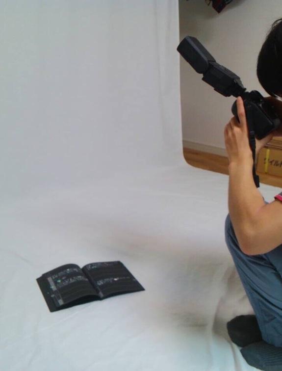 座り込んで手帳の写真を撮影している安藤