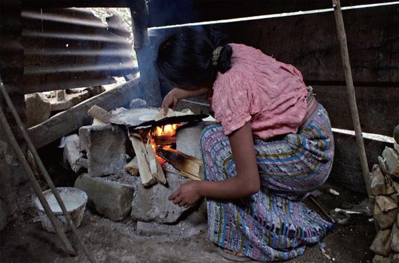 原始的なクック・ストーブで主食のトルティーヤを焼くお母さん