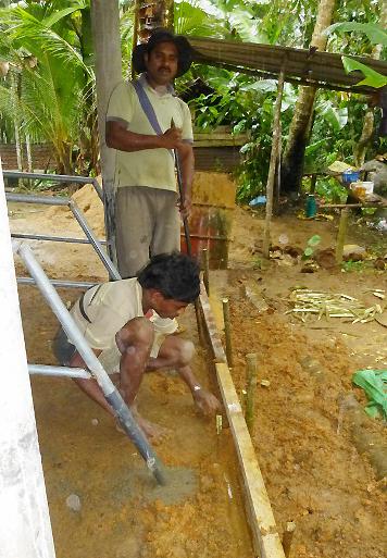 石工さんの指示の下、スタッフのサンパットくんのお兄さんが溝を作る準備をしています。