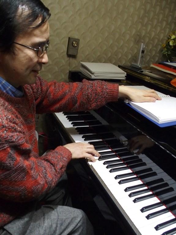 楽譜を読みながら片手でピアノで音を確認している写真